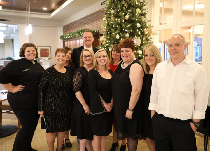 The Merrill Gardens at Madison team by the Christmas tree