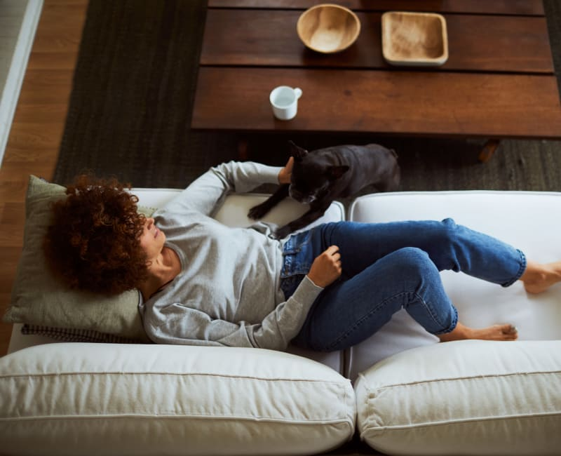 Resident and her dog relaxing in their new home at Santana Ridge in Denver, Colorado