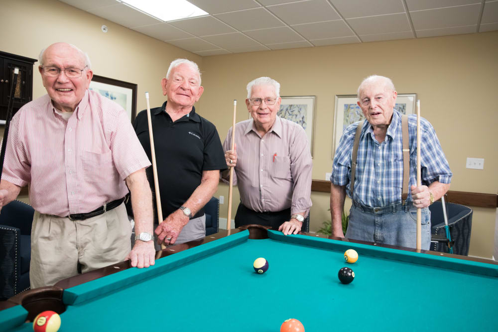 Smiling residents around a billiard table at The Heritage at Fountain Point in Norfolk, Nebraska