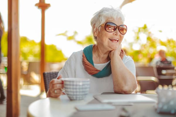 A resident enjoying a mug of coffee outside at Merrill Gardens at Brentwood in Brentwood, California.