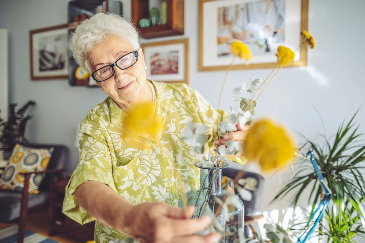 Resident arranging a flower pot at Bishop's Court in Allouez, Wisconsin