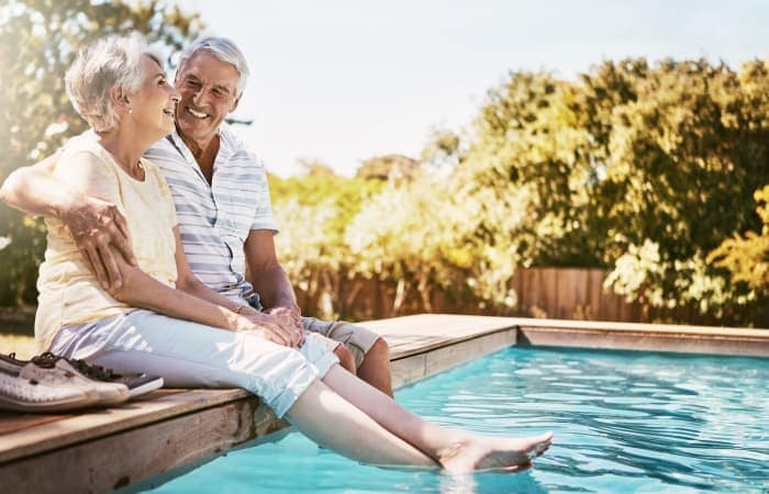 A couple by the pool on a sunny day at Widdicombe Place in Etobicoke