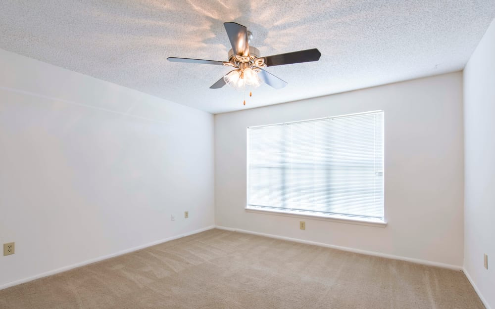 LIving room with plush carpeting and ceiling fans at Compass in Melbourne, Florida