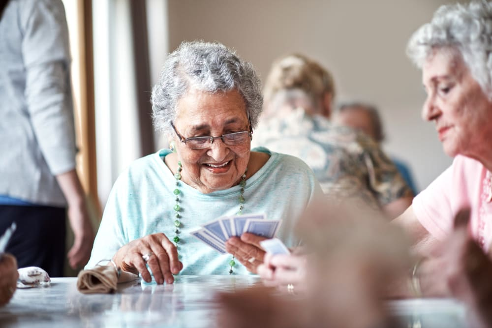 Happy resident in the lounge playing cards at Shadow Mountain Memory Care in Phoenix, Arizona