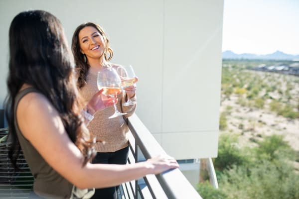 Residents enjoying a glass of wine on their private balcony at The Retreat at the Raven in Phoenix, Arizona