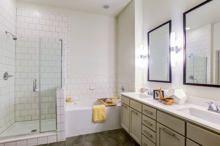 Tiled shower with an oval bathtub and a large vanity mirror in a model home's bathroom at Agave in San Antonio, Texas