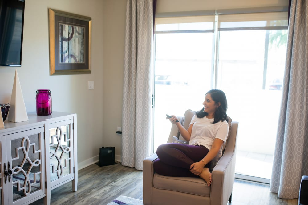Resident watching TV in her new apartment home at The Retreat at the Raven in Phoenix, Arizona
