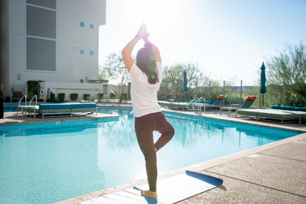 Resident doing some yoga near the pool at The Hyve in Tempe, Arizona