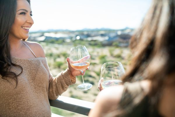 Residents enjoying a glass of wine on their private balcony at San Lagos in Glendale, Arizona