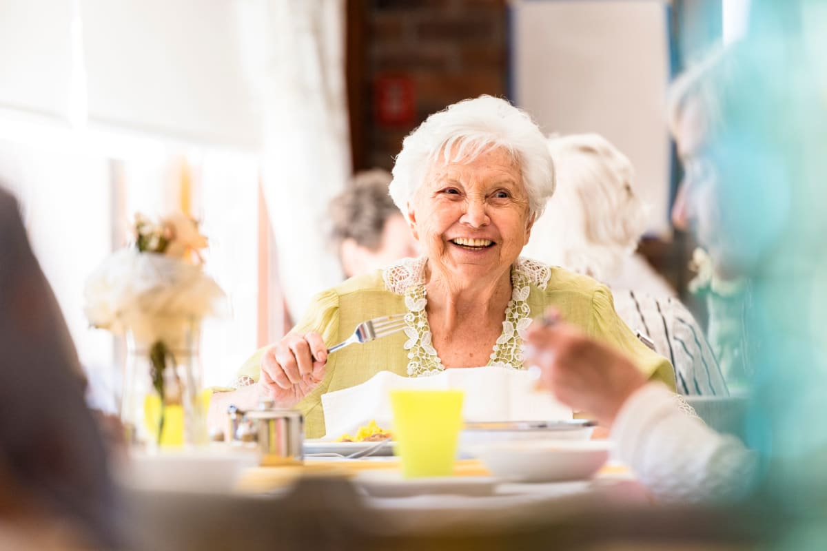 Resident smiling at the breakfast table at The Crossings at Bon Air in Richmond, Virginia