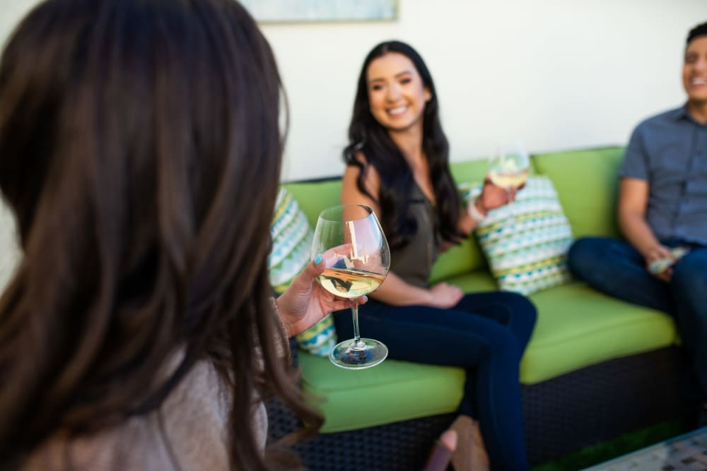 Residents drinking wine on their private balcony at Club Cancun in Chandler, Arizona