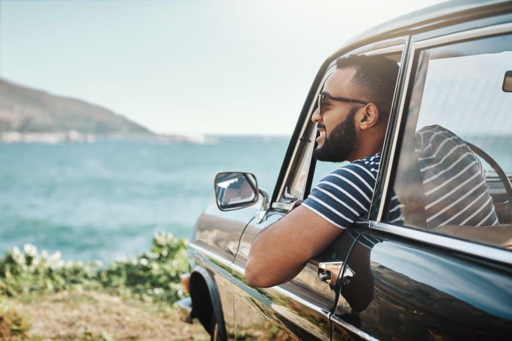 A man hanging out of his car by the coast near Hayward Storage LLC in Hayward, California