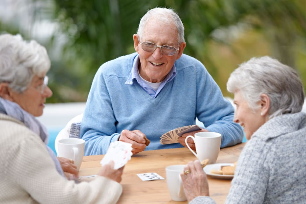 Residents playing a game on outdoor patio at Milestone Senior Living in Faribault, Minnesota.