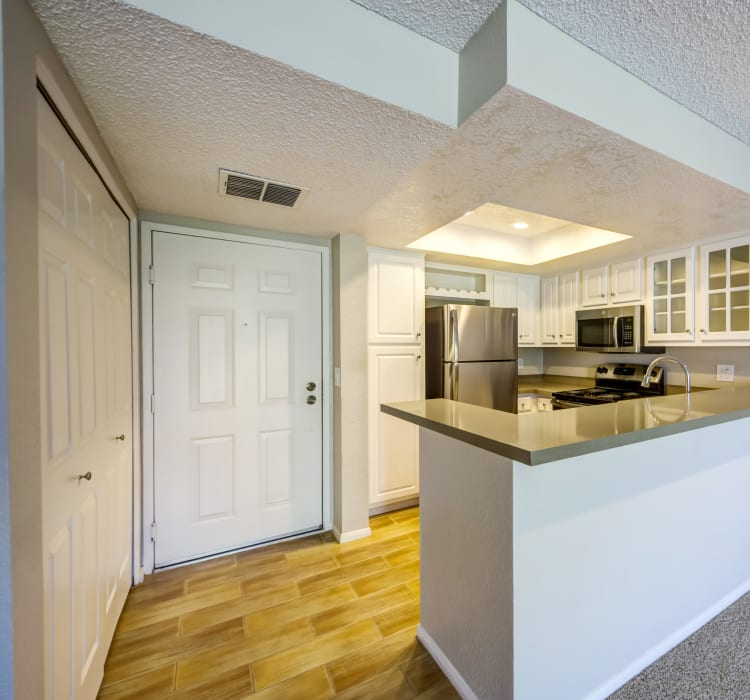 Model home's entryway and kitchen with hardwood flooring at Sofi Irvine in Irvine, California