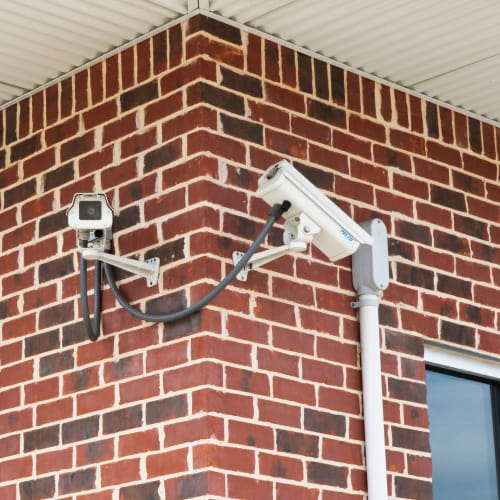 Security cameras mounted on a brick wall at Red Dot Storage in Cedar Falls, Iowa
