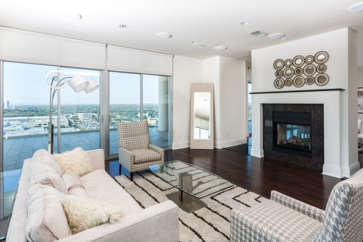 Living room with fireplace at The Heights at Park Lane in Dallas, Texas