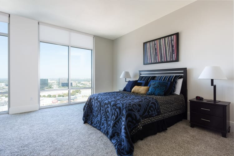Bedroom with dark bed and light walls at The Heights at Park Lane in Dallas, Texas