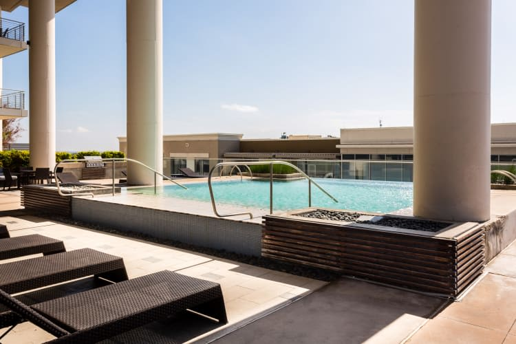 Outdoor pool with patio seating at The Heights at Park Lane in Dallas, Texas