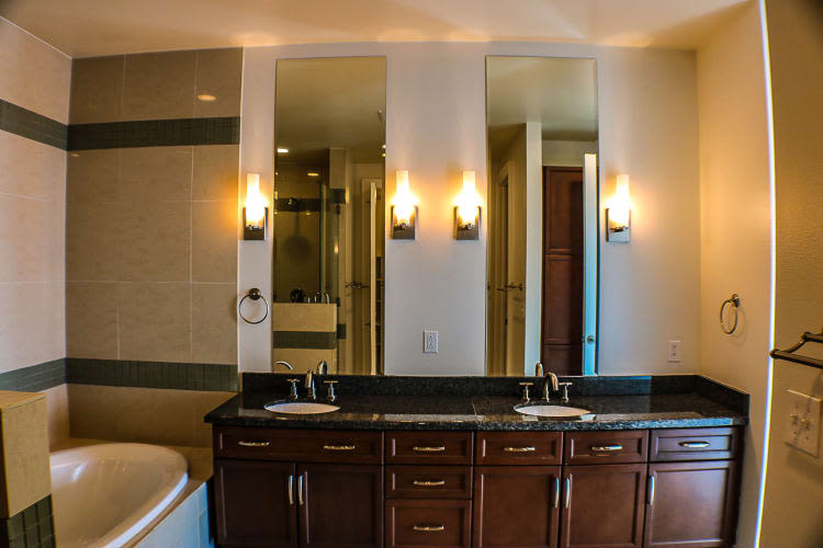 Bathroom with tiled bathtub at The Heights at Park Lane in Dallas, Texas
