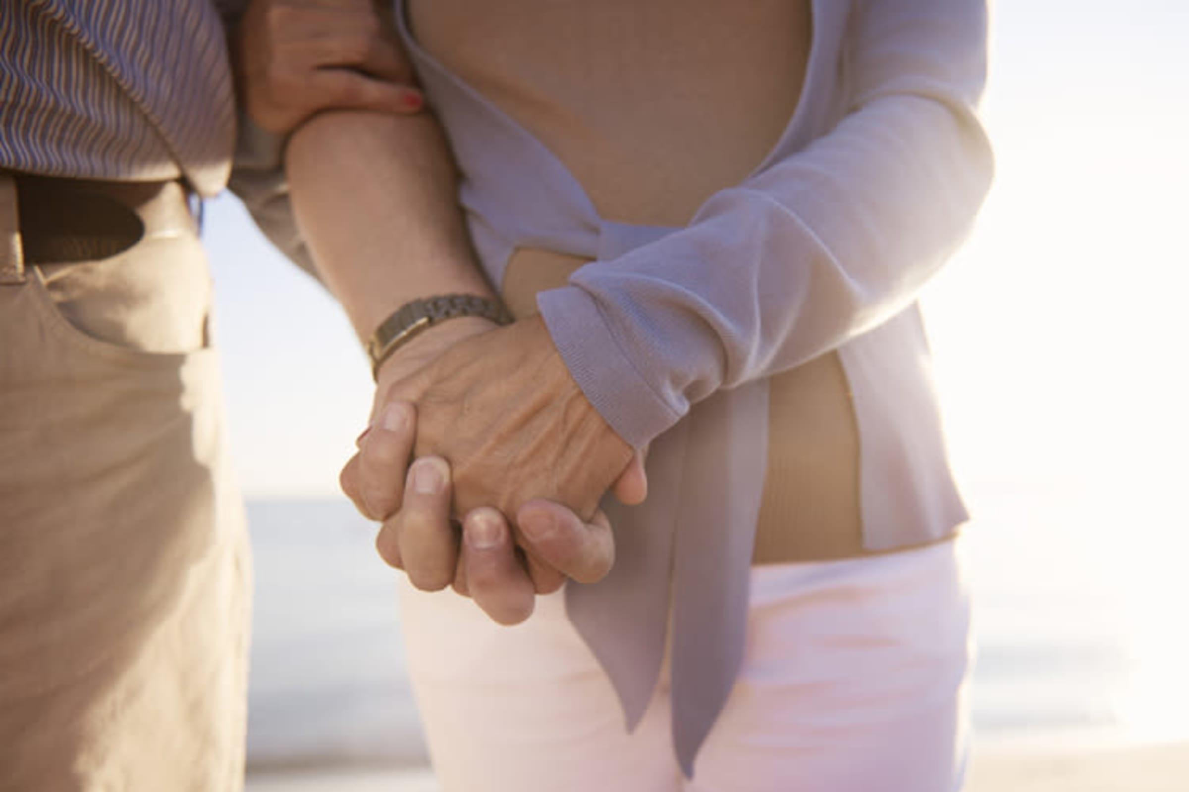 Seniors holding hands on the beach at Estancia Del Sol in Corona, California