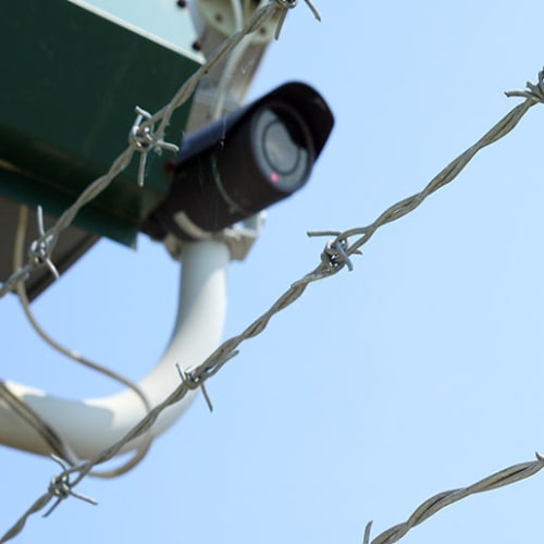 Security camera with barbed wire fencing at Red Dot Storage in Hot Springs, Arkansas