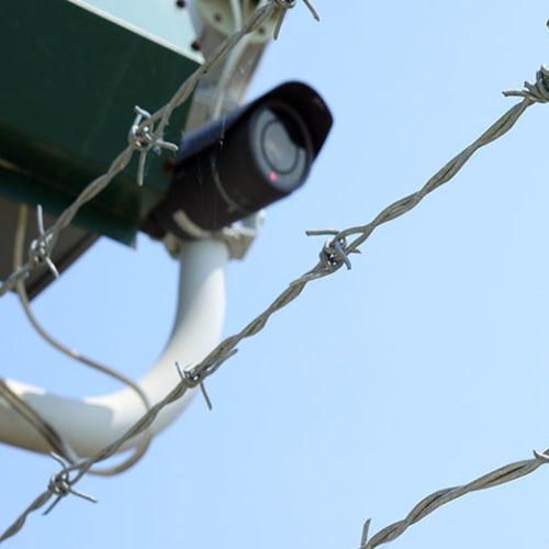 Security camera behind a barbed wire fence at Red Dot Storage in Port Allen, Louisiana