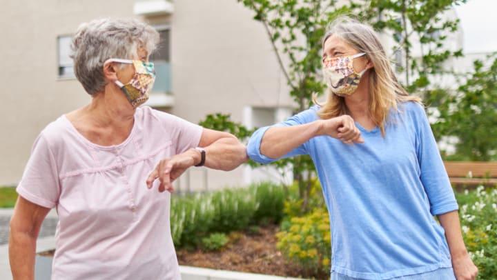 Seniors in masks touching elbows
