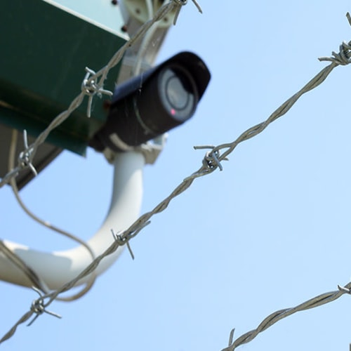 Security camera behind barbed wire fence at Red Dot Storage in Searcy, Arkansas