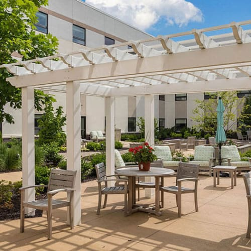 Outdoor patio seating with pergola at First & Main of Auburn Hills in $Auburn Hills, Michigan