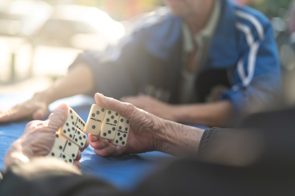 An elderly resident playing dominoes at Stoney Brook of Belton in Belton, Texas