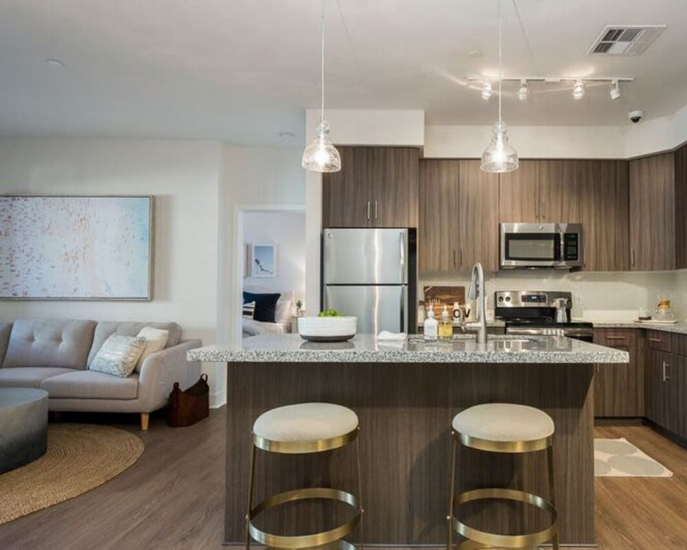 Beautiful gourmet kitchen next to the living area of an open-concept model home at Cadia Crossing in Gilbert, Arizona