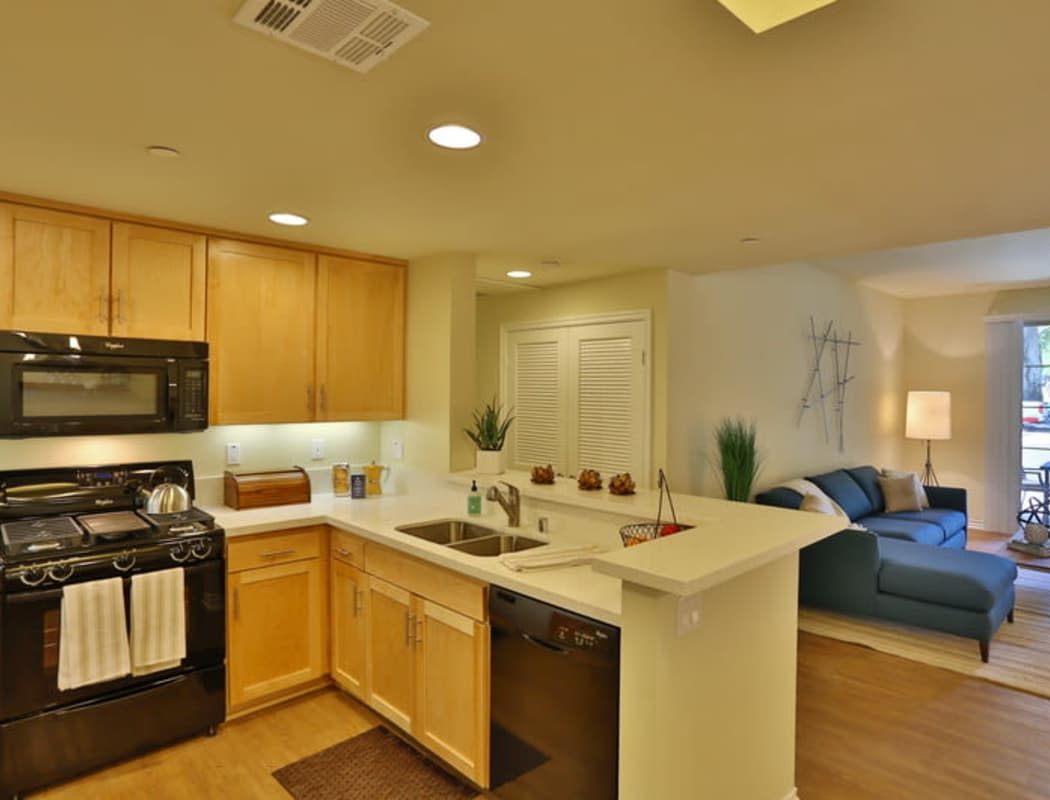 Model apartment kitchen looking into living area at IMT Park Encino in Encino, California