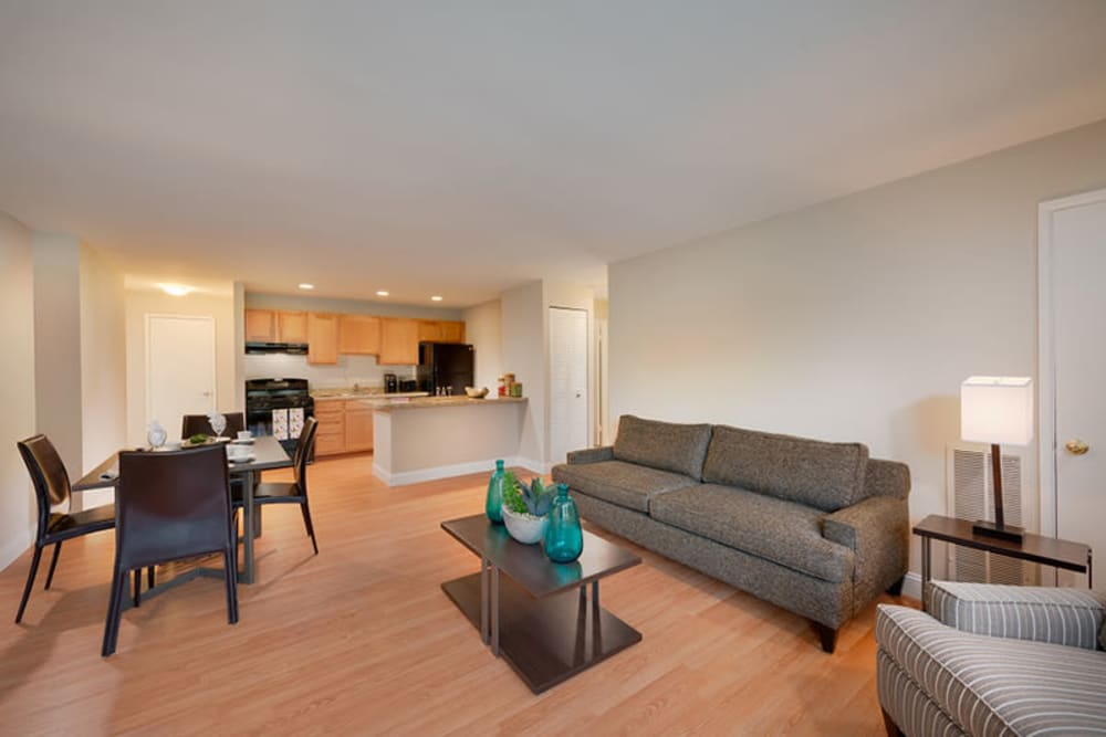 An open-concept living room with wood-style flooring at The Landings I & II Apartments in Alexandria, Virginia