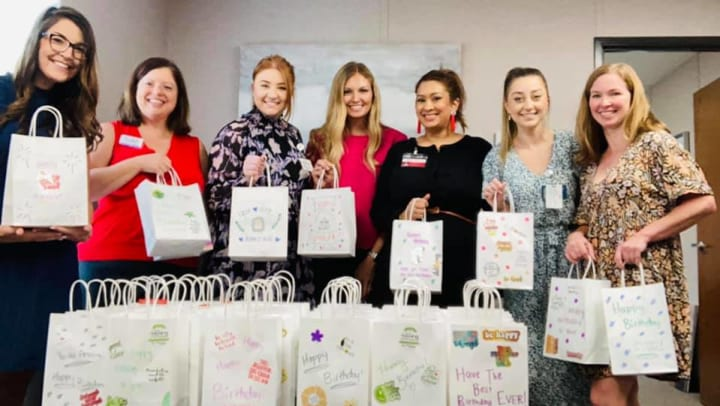 women smiling and holding gift bags