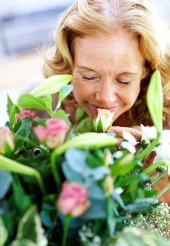 A resident smelling flowers near The Claiborne at Hattiesburg Assisted Living in Hattiesburg, Mississippi.