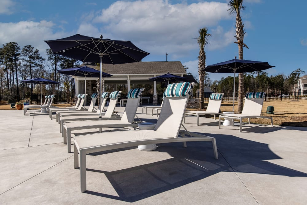 Pool lounge chairs at South City Apartments in Summerville, South Carolina
