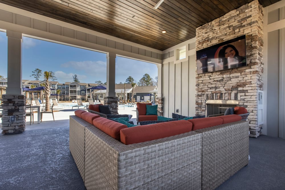 Outdoor lounge seating with TV at South City Apartments in Summerville, South Carolina