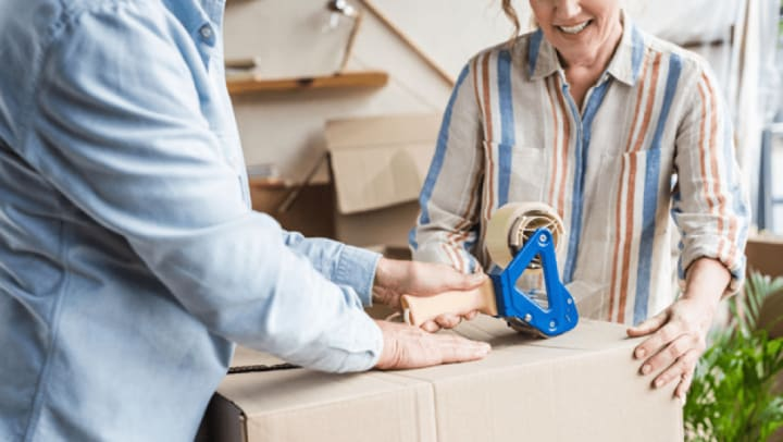 Couple taping a packing box
