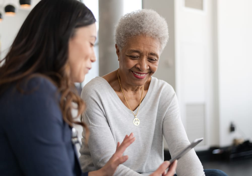 Staff member going over electronic records with a resident at Inspired Living Sugar Land in Sugar Land, Texas.
