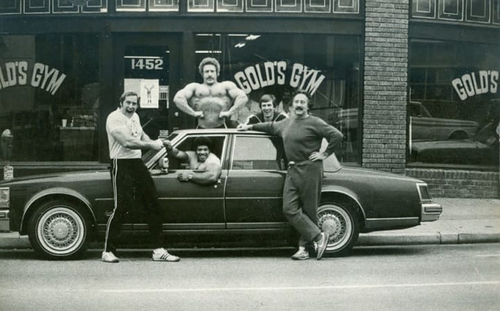 Vintage photograph of five body builders taken in front of Golds Gym.