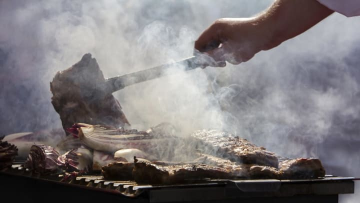 Resident cooking up some ribs on the barbecue grills at Olympus Sierra Pines in The Woodlands, Texas
