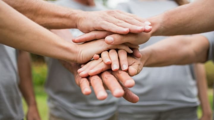 Volunteers clasping hands at Legends at White Oak in Ooltewah, Tennessee
