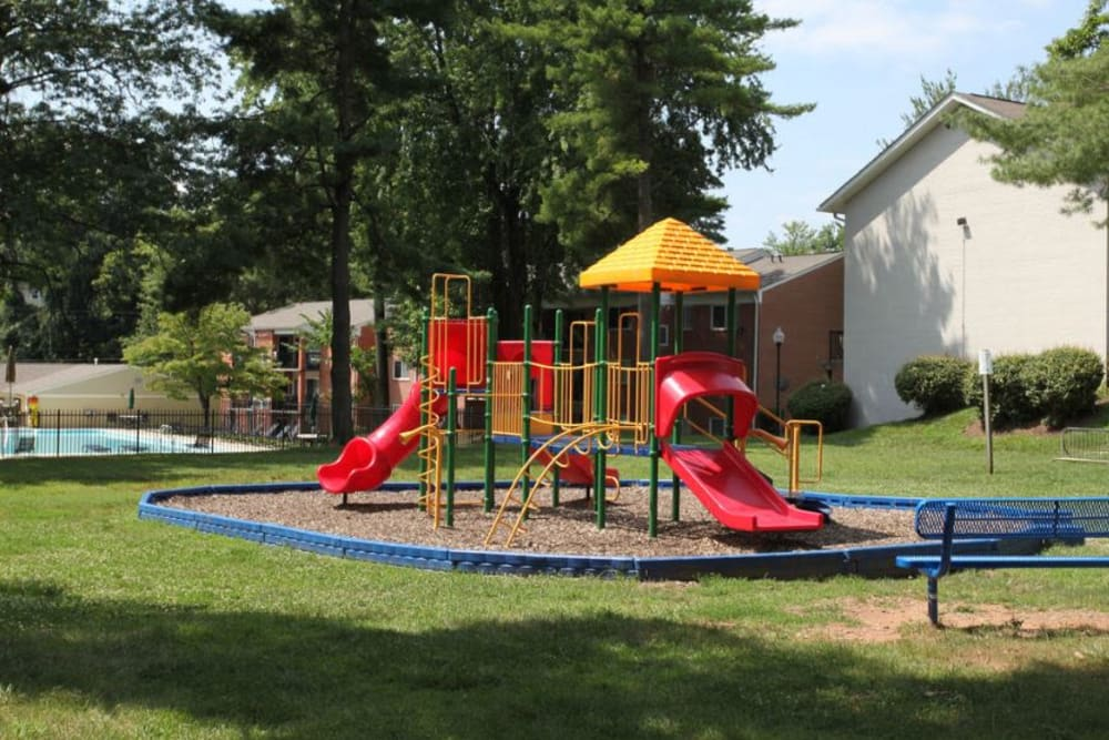Children's playground surrounded by a lush grass lawn at Glenmont Crossing in Wheaton, Maryland