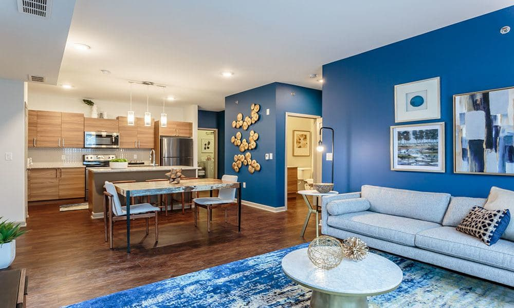 Spacious living area with an accent wall in the open-concept layout of a model home at GrandeVille at Malta in Malta, New York