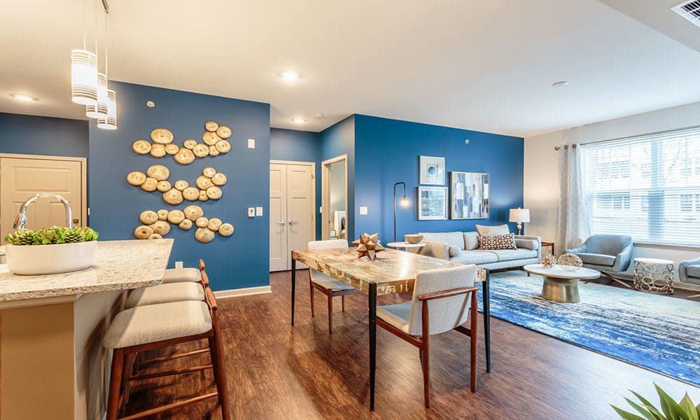 Hardwood floors and modern decor in the living area of a model home at GrandeVille at Malta in Malta, New York