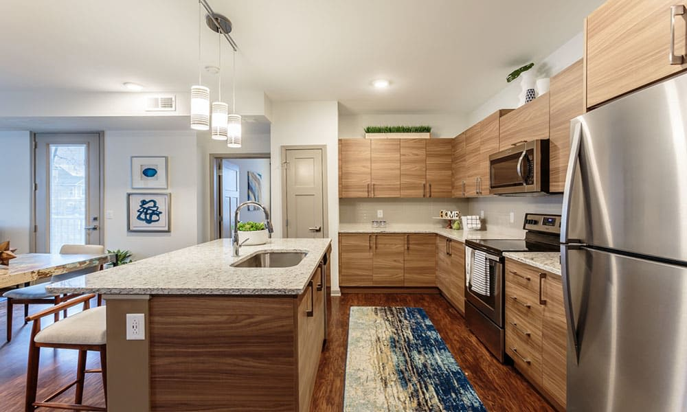Modern kitchen with custom cabinetry and quartz countertops in a model home at GrandeVille at Malta in Malta, New York