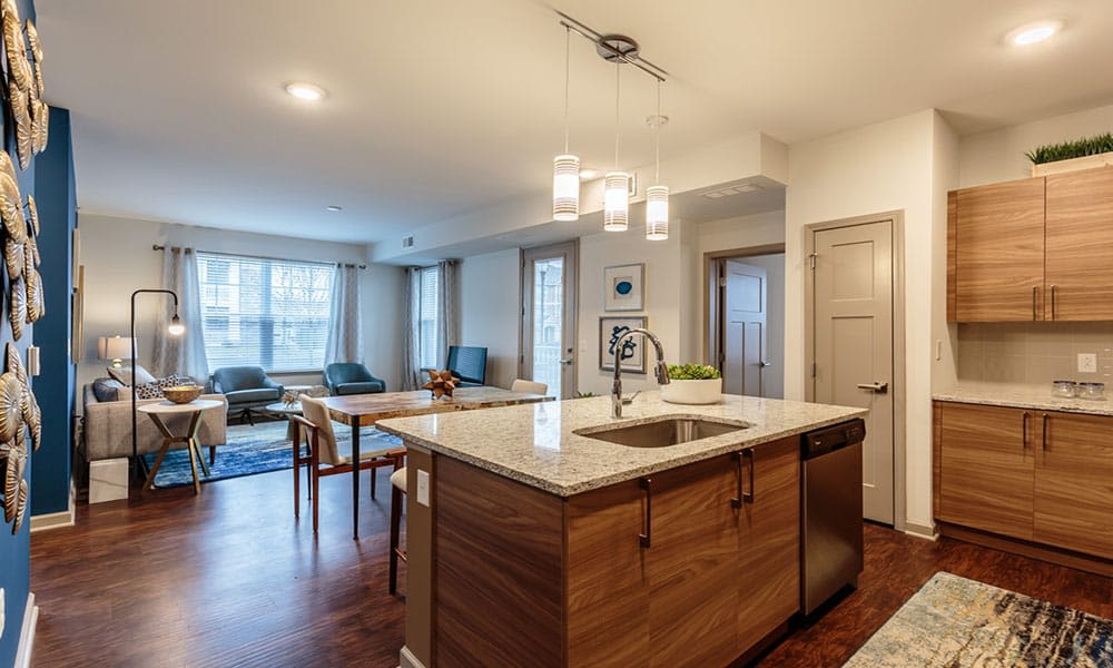 View of the living area from a model home's kitchen in the open-concept floor plan of a model home at GrandeVille at Malta in Malta, New York