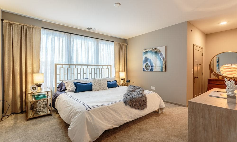 Spacious bedroom with plush carpeting and large windows in a model home at GrandeVille at Malta in Malta, New York