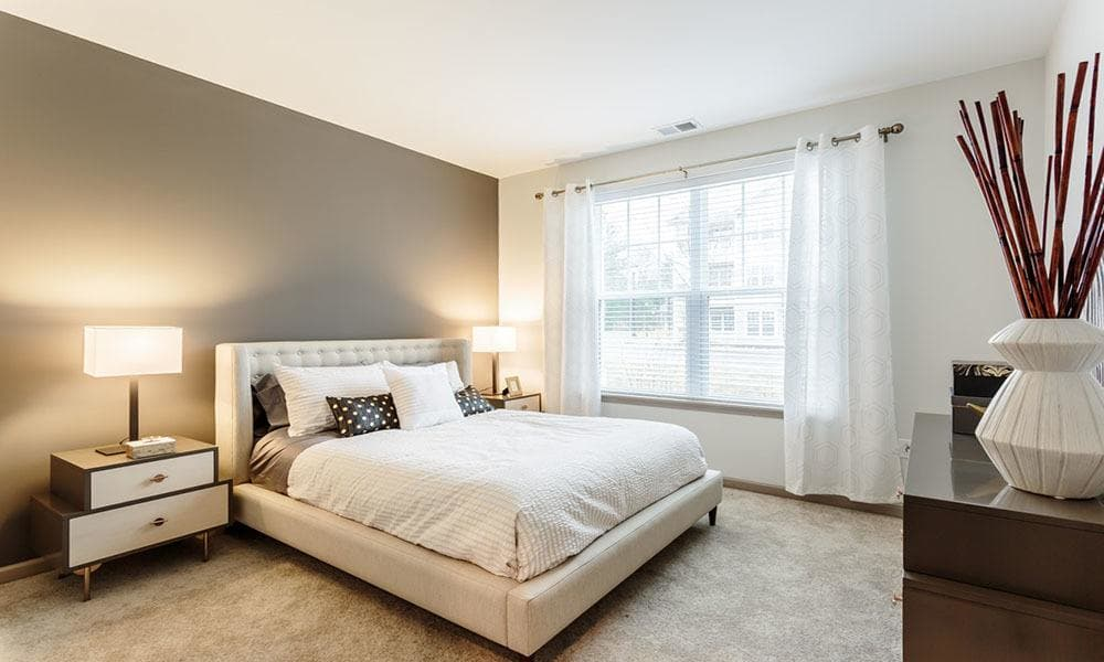 Well-decorated bedroom in a model home at GrandeVille at Malta in Malta, New York