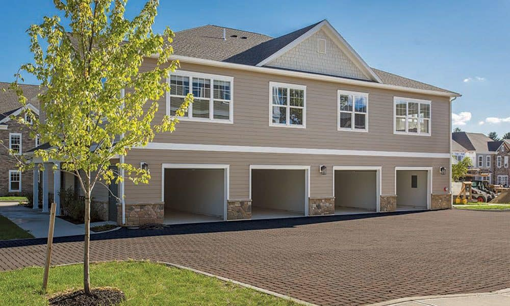 Well-manicured landscaping outside resident buildings with attached garages at GrandeVille at Malta in Malta, New York